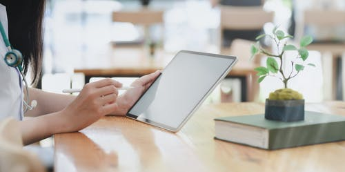 Person Leaning On Wooden Table Holding White Tablet