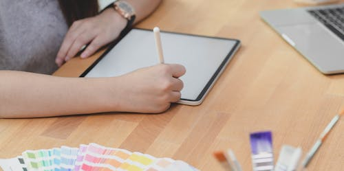 Photo Of Person Using Tablet