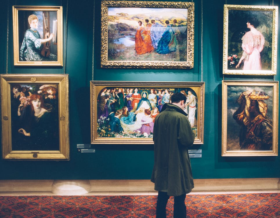 Man Standing in Front of Paintings