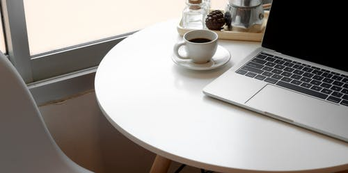 Espresso Beside Laptop On Round Table
