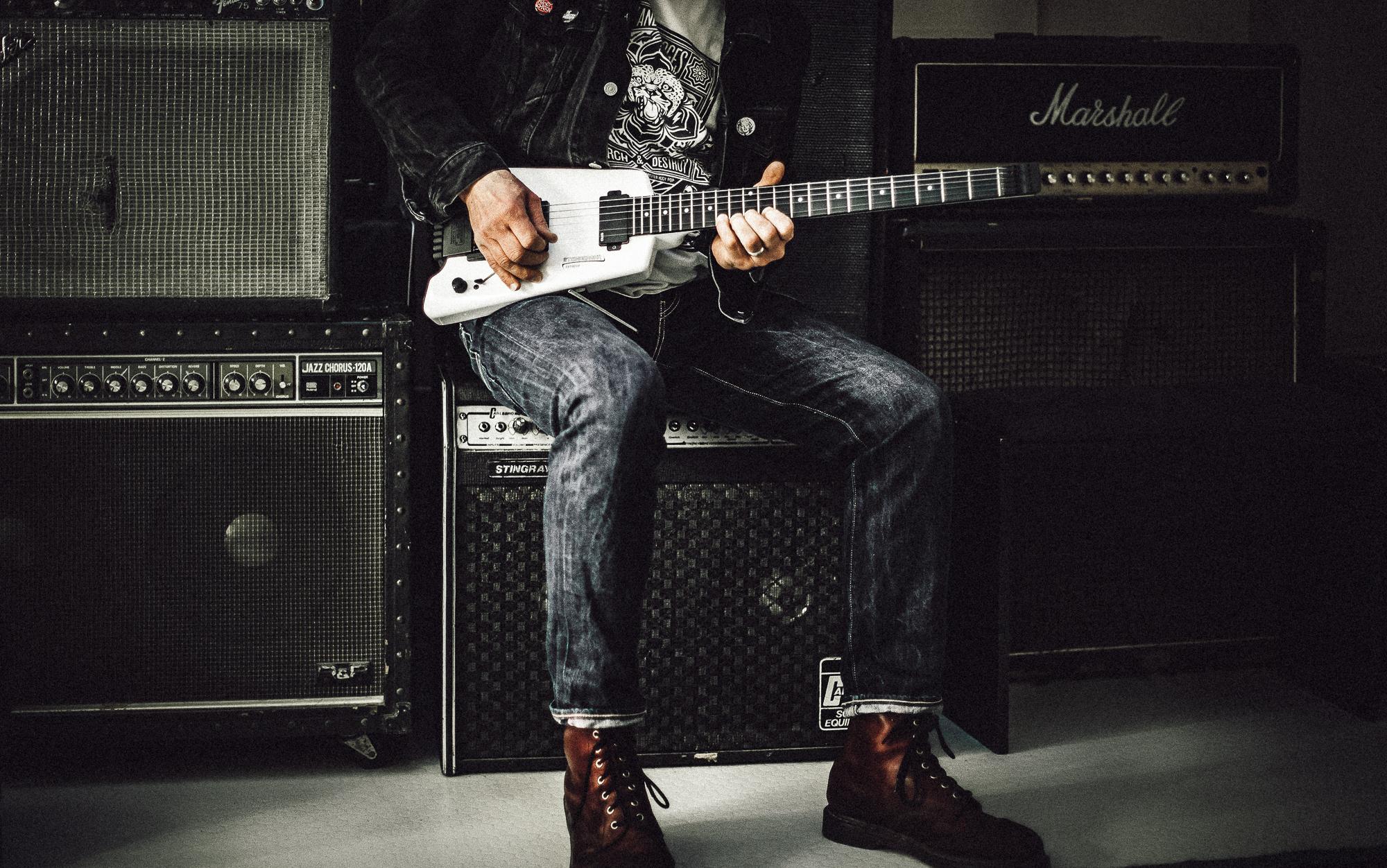 Man Sitting on Guitar Amplifier Playing Electric Guitar