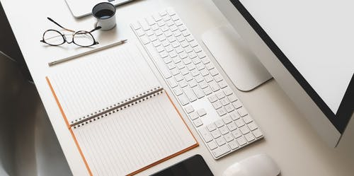 White Apple Keyboard on White Table