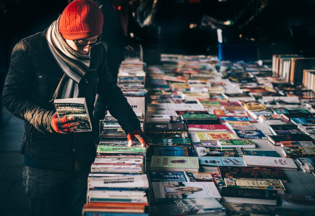 Person Holding Book While Browsing on Book Lot