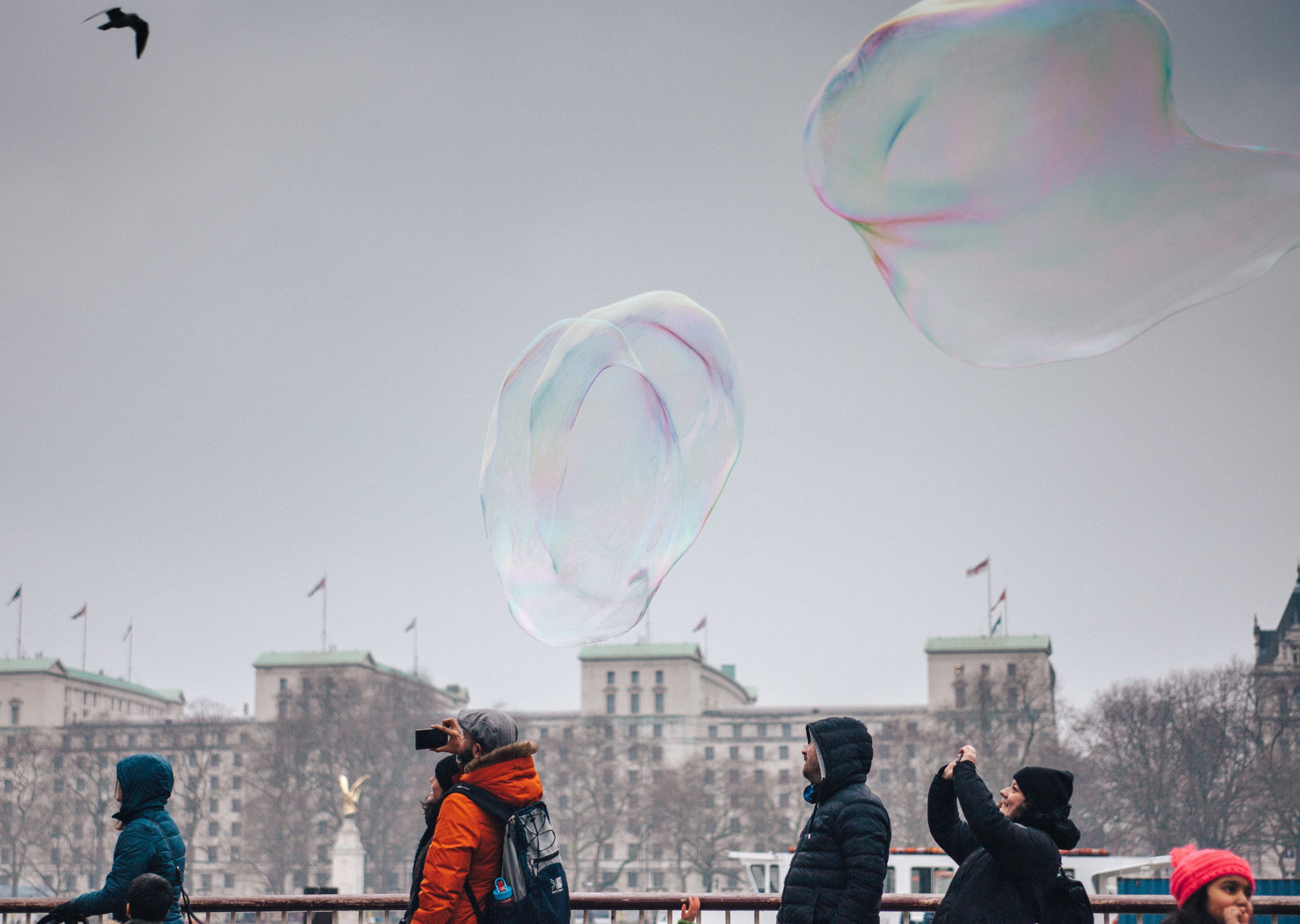 People Taking Photograph of Bubbles Floating Midair