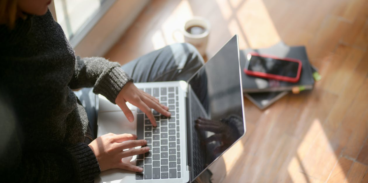 Woman in Gray Sweater Typing On Laptop