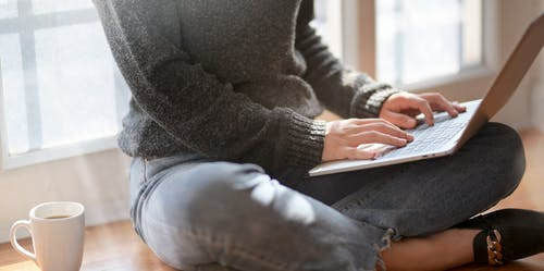 Photo of Person in Black Sweater and Blue Denim Jeans Sitting on Brown Wooden Floor While Using a Laptop