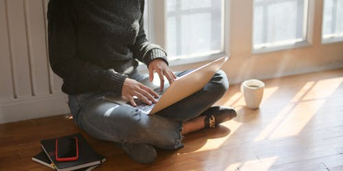 Photo of Woman in Black Sweater and Blue Denim Jeans Sitting on Brown Wooden Floor While Using a Laptop