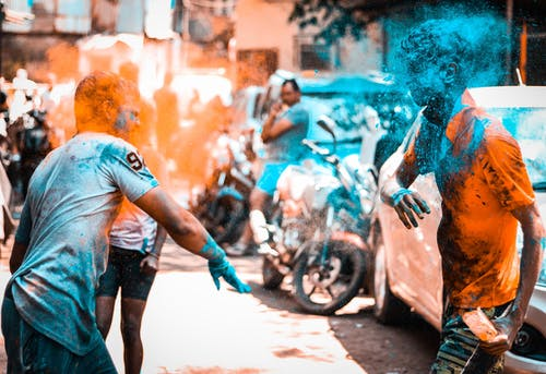 Joyful people throwing colored powders while celebrating Holi festival