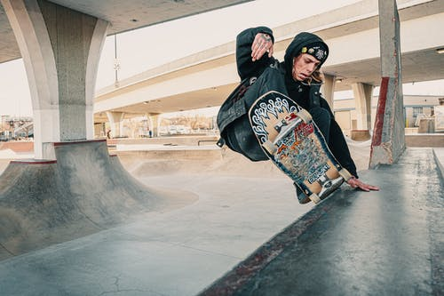 Photo of Man in Black Hoodie Doing a Skateboarding Trick at at Skate Park