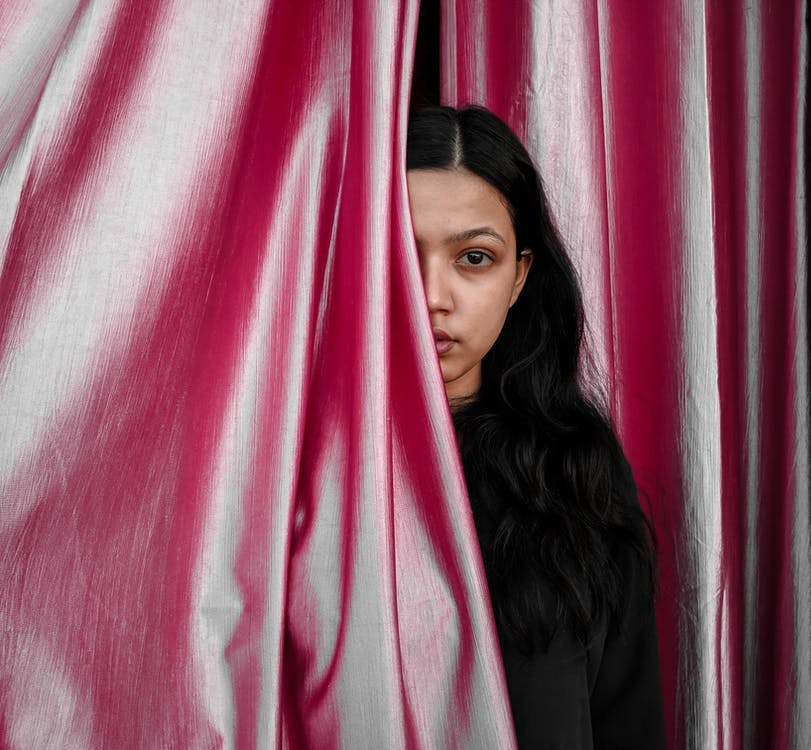 Photo of Woman in Black Top Standing Beside Pink Curtain With Part of Her Face Hidden