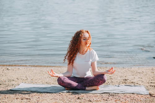 Woman Doing Yoga Exercise At The Sea Shore