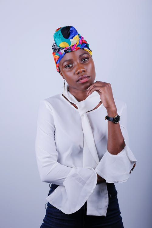 Photo of Woman in White Long Sleeve Shirt, Multicolored Headscarf, and Black Pants Posing In Front of White Background