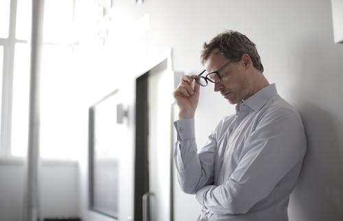 Photo Of Man Holding Black Eyeglasses