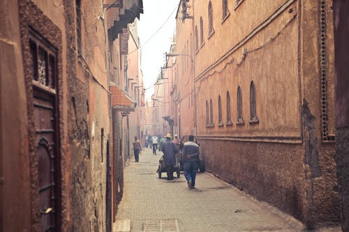 Pedestrians on narrow street of ancient city