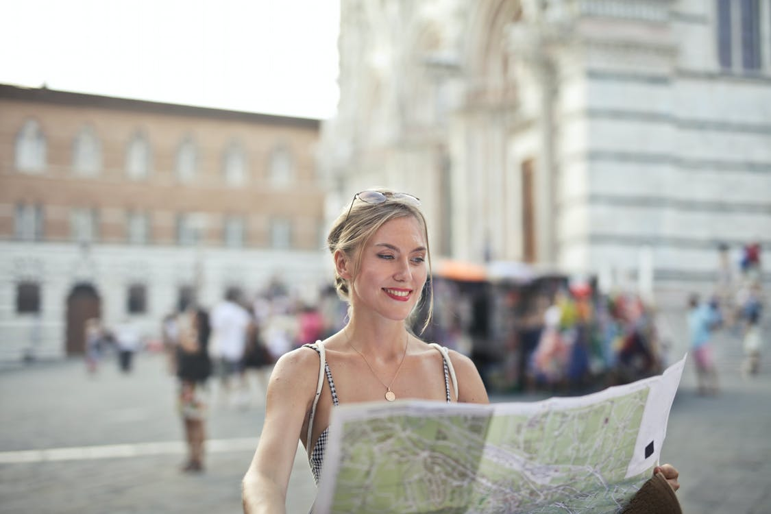 Woman Holding A Map Looking For Next Destination