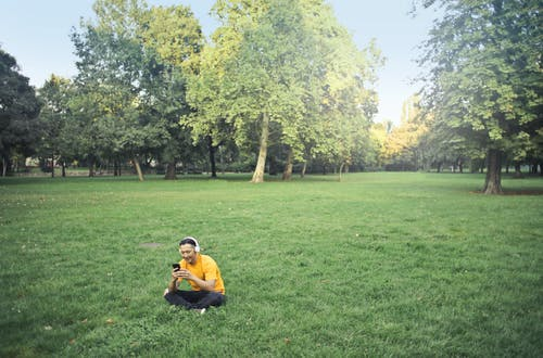 Photo of Man in Yellow T-shirt and Black Pants Sitting on Green Grass Field While Listening to Music on Headphones and Using His Phone