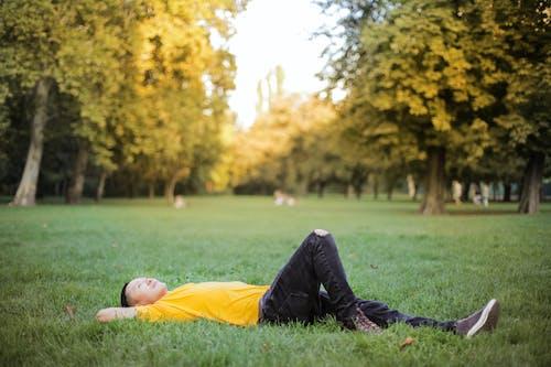 Foto Van Man In Geel T Shirt En Zwarte Spijkerbroek Liggend Op Groen Grasveld Met