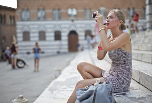 Selective Focus Photo of Woman in a Striped Dress Sitting on Concrete Stairs While Applying Lipstick
