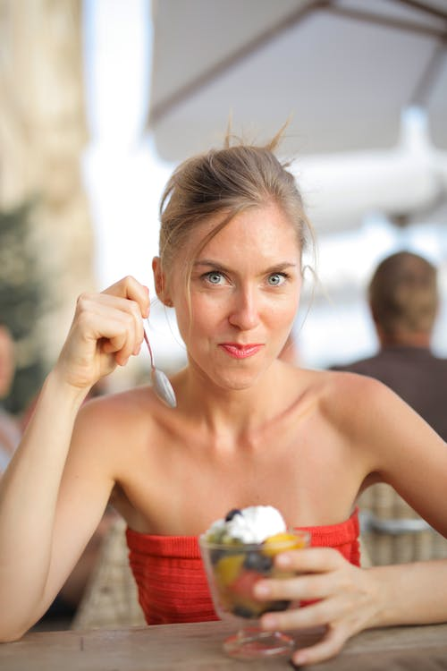 Selective Focus Photo of Smiling Woman in Red Tube Top Eating Dessert