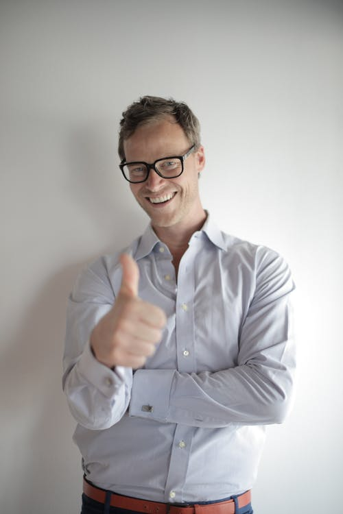 Photo of Smiling Man in Blue Dress Shirt and Black Framed Eyeglasses Giving Thumbs up