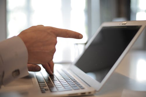 Photo of Person Pointing On Laptop