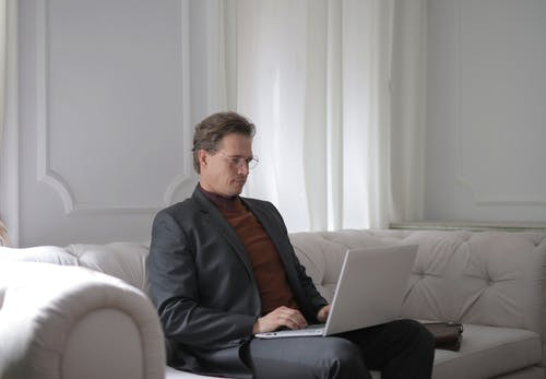 A Man Sitting on a White Couch Using Laptop