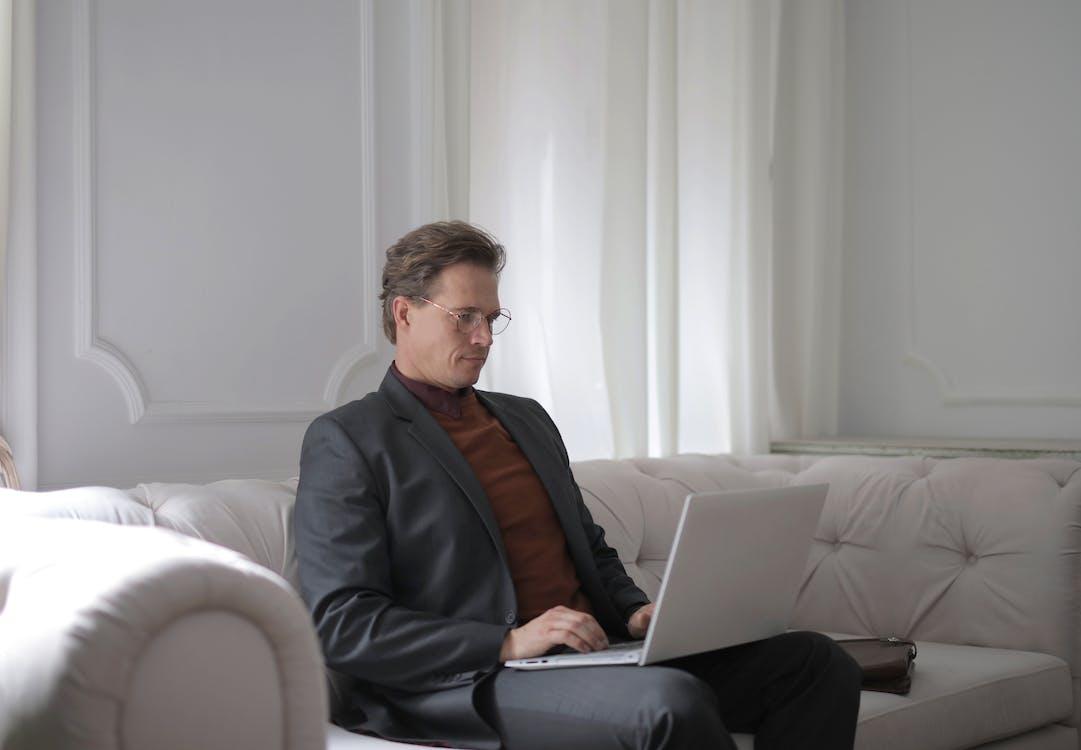 Seorang Pria Duduk Di Sofa Putih Menggunakan Laptop