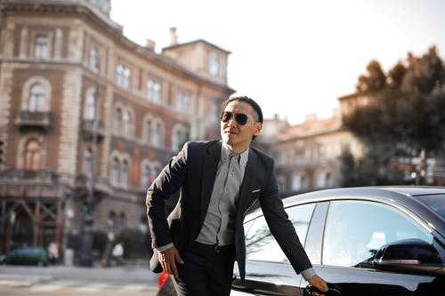 Photo of Man in Black Suit and Sunglasses Standing Beside Parked Car