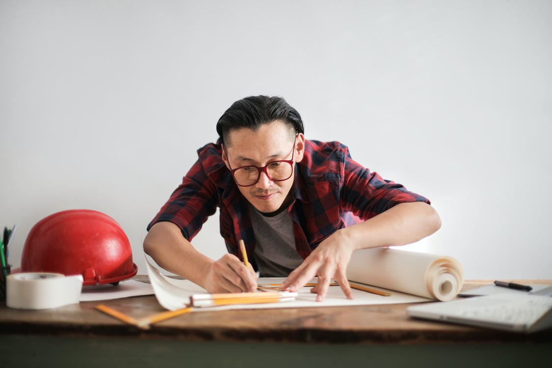 Inspired young male engineer in glasses drawing draft on paper bending over table against white wall