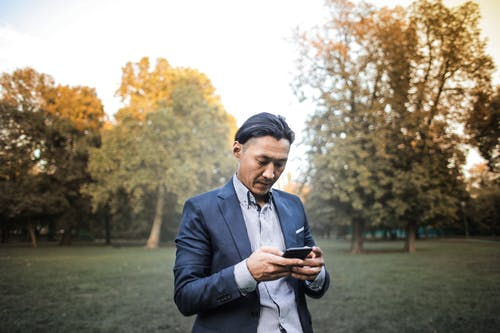 Photo of Man in Suit Jacket and Striped Shirt Using His Phone