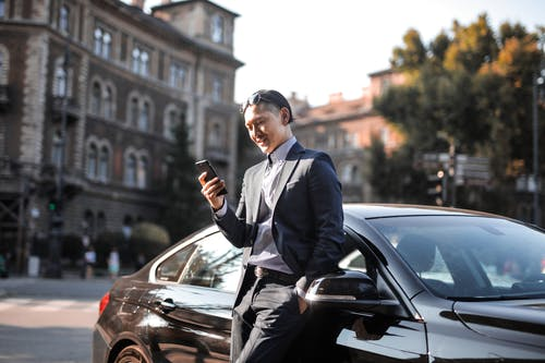 Selective Focus Photo of Man in Black Suit Using His Phone While Leaning Beside Black Car