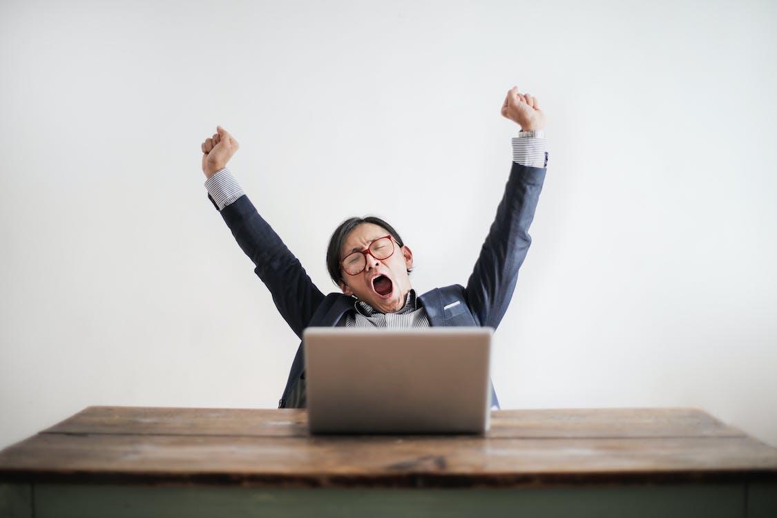 Фотография зевающего мужчины с поднятыми руками и закрытыми глазами, сидящего за столом со своим ноутбуком