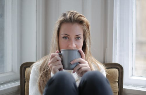 Photo of Woman Sitting in a Chair Holding Gray Ceramic Mug