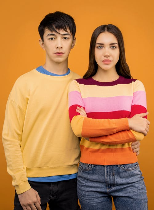 Photo of Woman in Multicolored Striped Sweatshirt Standing Beside Man in Yellow Sweatshirt In Front of Orange Background