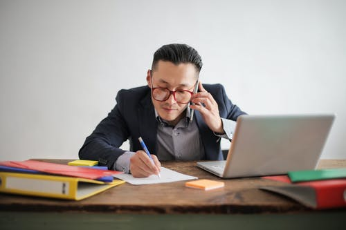 Photo of Man in Blue Suit Jacket,Striped Shirt, and Eyeglasses Talking on the Phone While Sitting at a Table With His Laptop