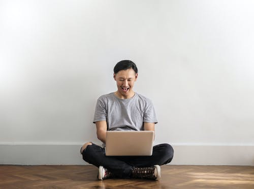 Photo of Laughing Man in Gray T-shirt and Black Jeans on Sitting on Wooden Floor While Using a Laptop