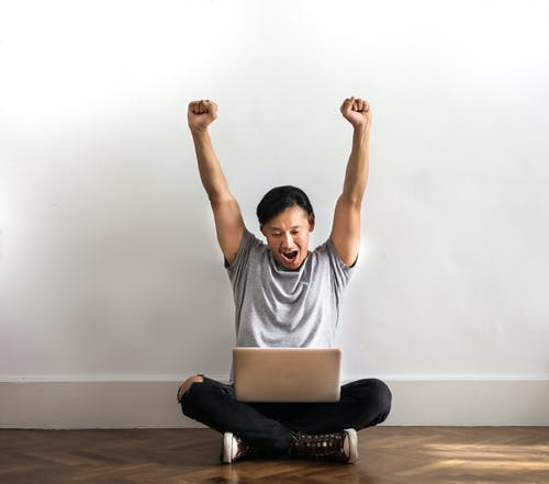 Photo of Man in Gray T-shirt and Black Pants Sitting on Wooden Floor and Working on His Laptop Celebrating with His Hands Raised