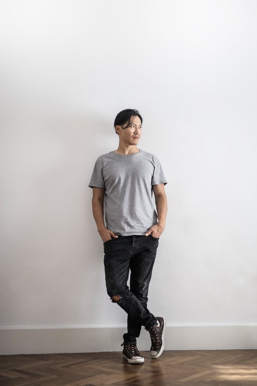 Photo of Man in Gray T-shirt and Black Denim Jeans Standing In Front of Gray Wall