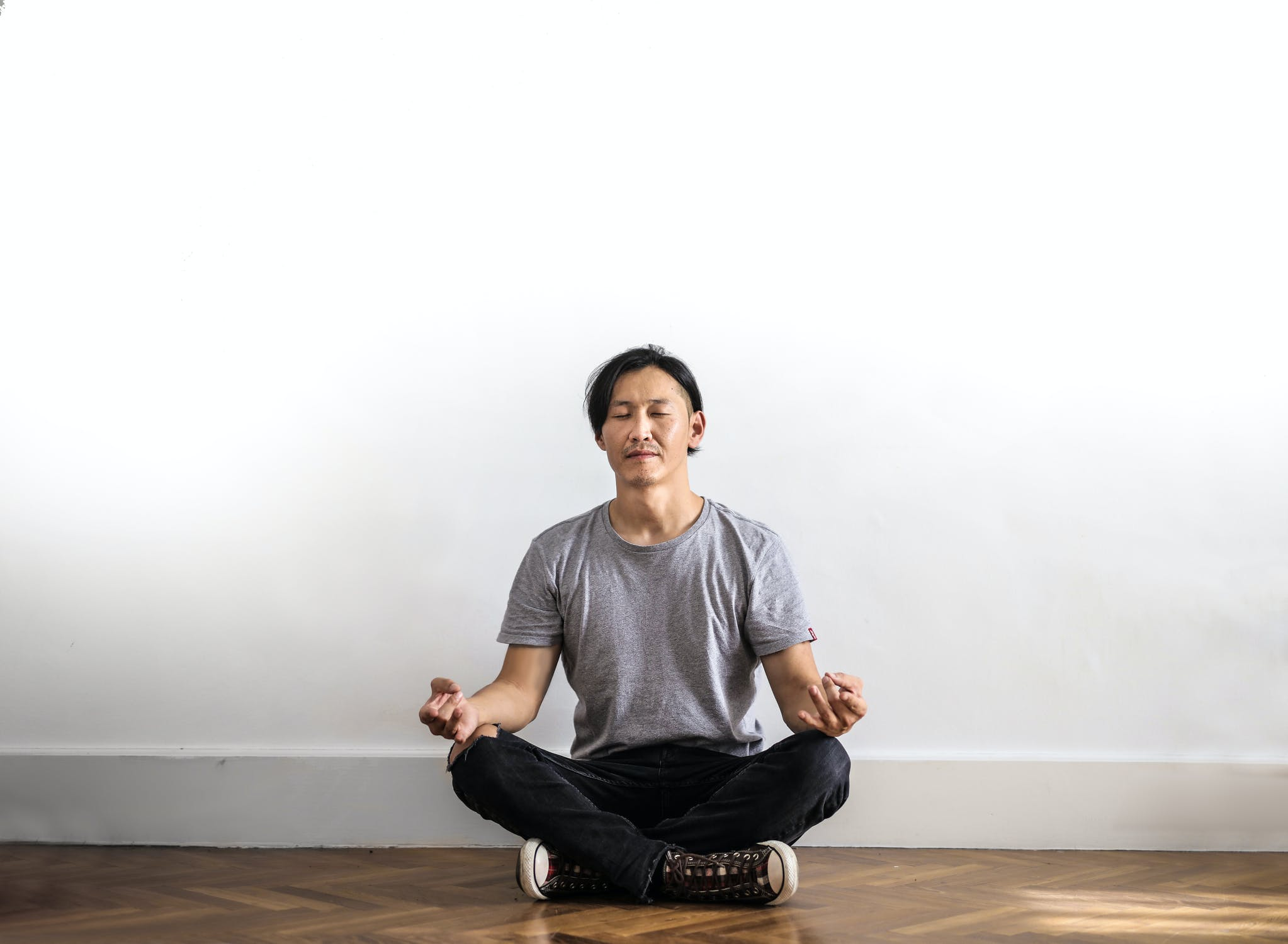 A man meditating in an open room. Photo by pexels user Andrea Piacquadio. Used courtesy of Pexels.com