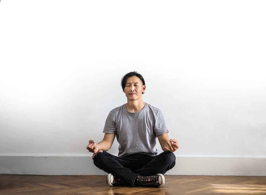 Photo of Man in Gray T-shirt and Black Jeans on Sitting on Wooden Floor Meditating