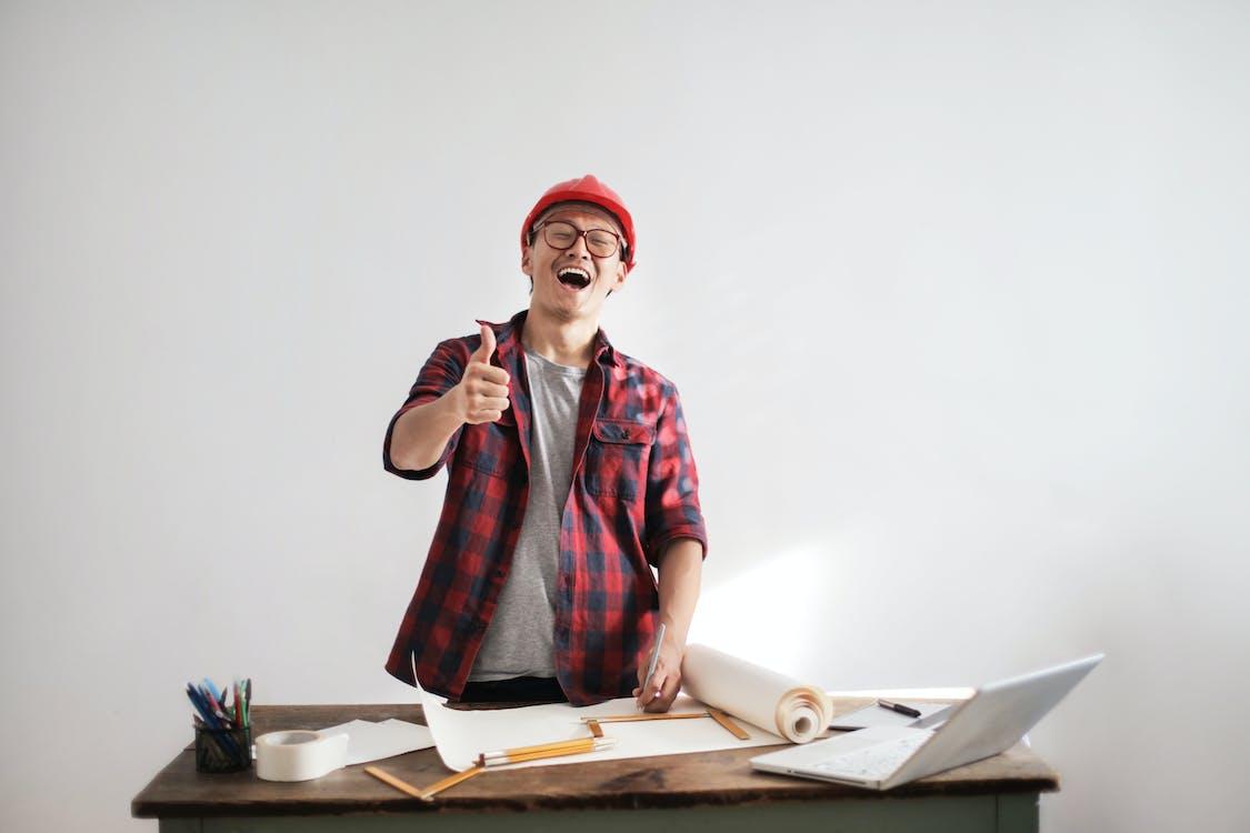 Constructor Masculino Riendo Mostrando El Pulgar Hacia Arriba En La Mesa De Trabajo