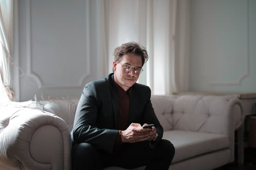 Photo of Smiling Man in Black Suit Sitting on White Couch Using His Phone