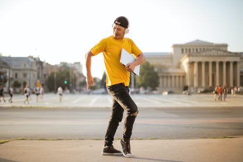 Selective Focus Photo of Man in Yellow T-shirt, Black Denim Jeans, and Headphones Dancing While Carrying a Laptop