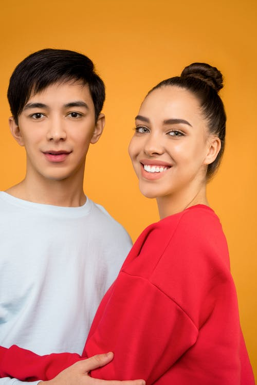 Portrait Photo of Man in White Crew Neck T-shirt Standing Beside Woman in Red Crew Neck T-shirt