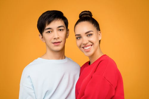 Photo of Man in White Sweatshirt Standing Beside Woman in Red Sweatshirt In Front of Orange Background