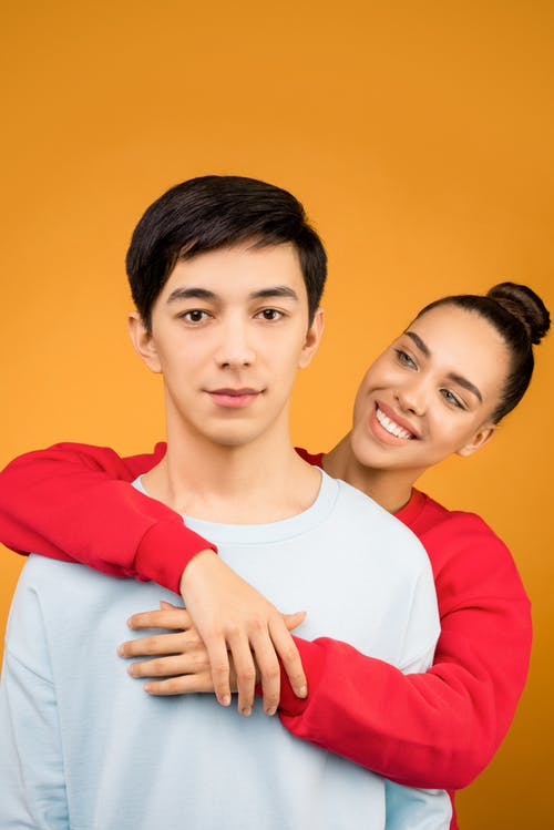 Photo of Smiling Woman Hugging Man from Behind