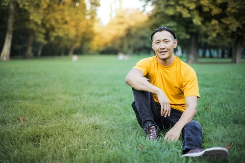 Man in Yellow Crew Neck T-shirt and Blue Denim Jeans Sitting on Green Grass Field