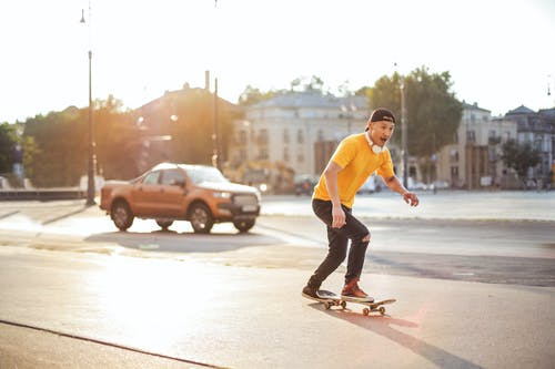 Man in Yellow Shirt and Black Pants Riding Skateboard