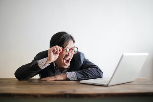Modern Asian man in jacket and glasses looking at laptop and screaming with mouth wide opened on white background