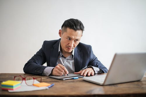 Man in Black Suit Jacket Using Macbook Pro